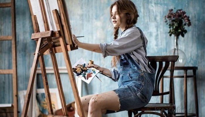 Девушка рисует красками на холсте картину