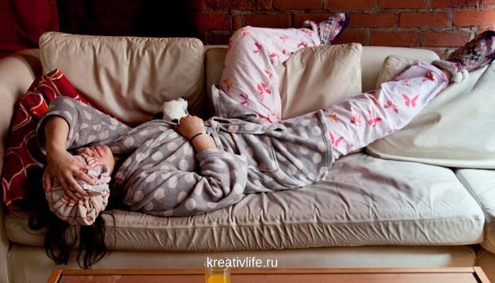 девушка устала и прилягла на диван с головной болью