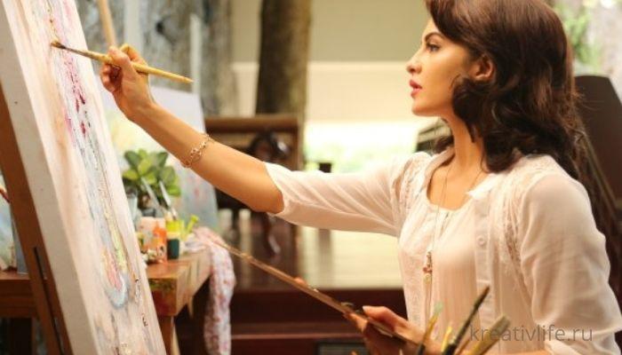 Девушка занимается творчеством . Рисует на холсте красками
